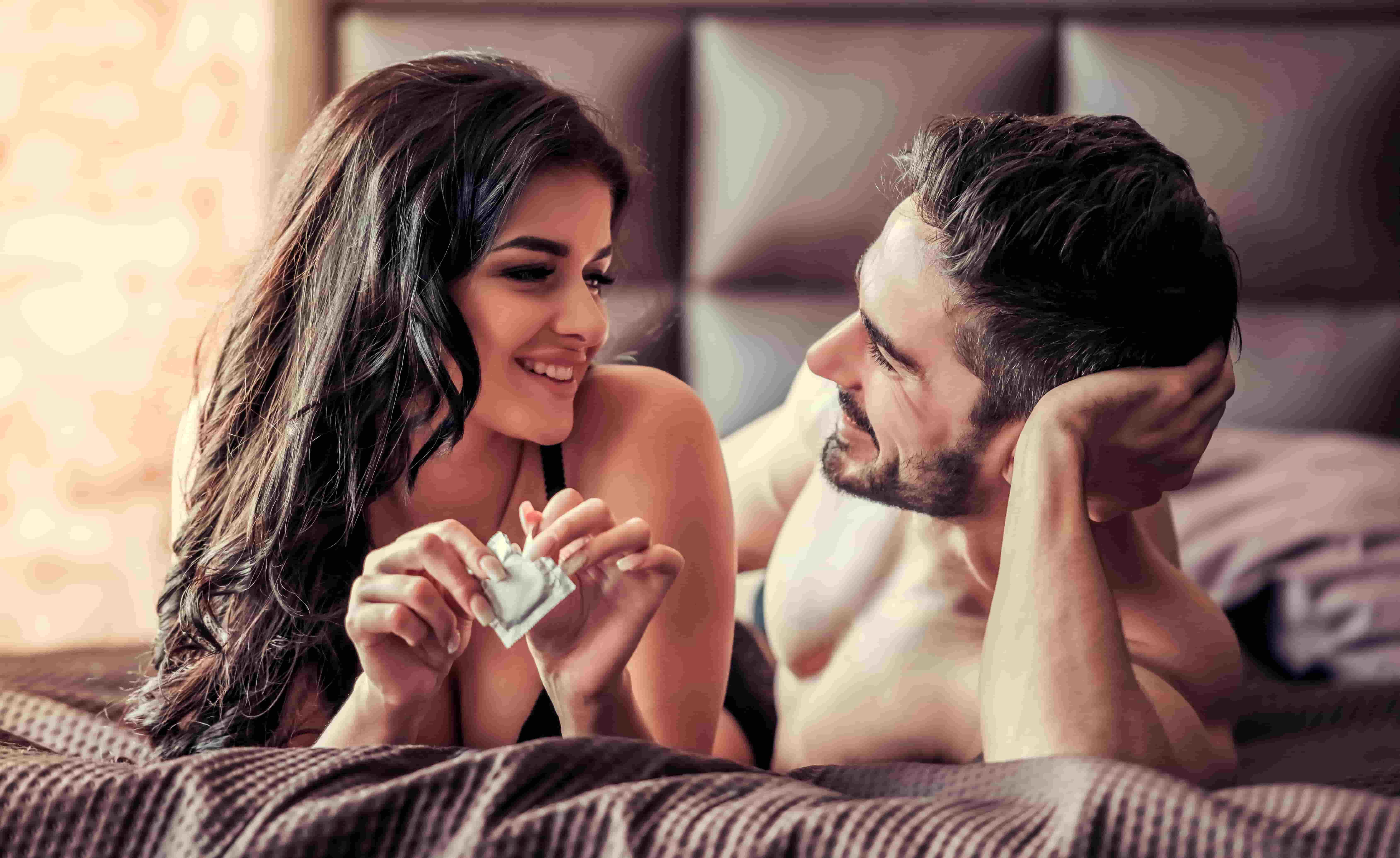 man and woman in bed woman holding condom