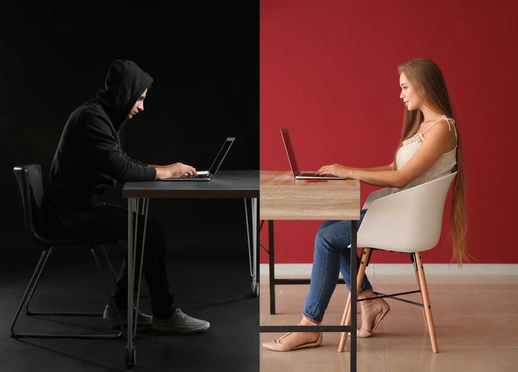 man in all black on computer girl on computer on other side