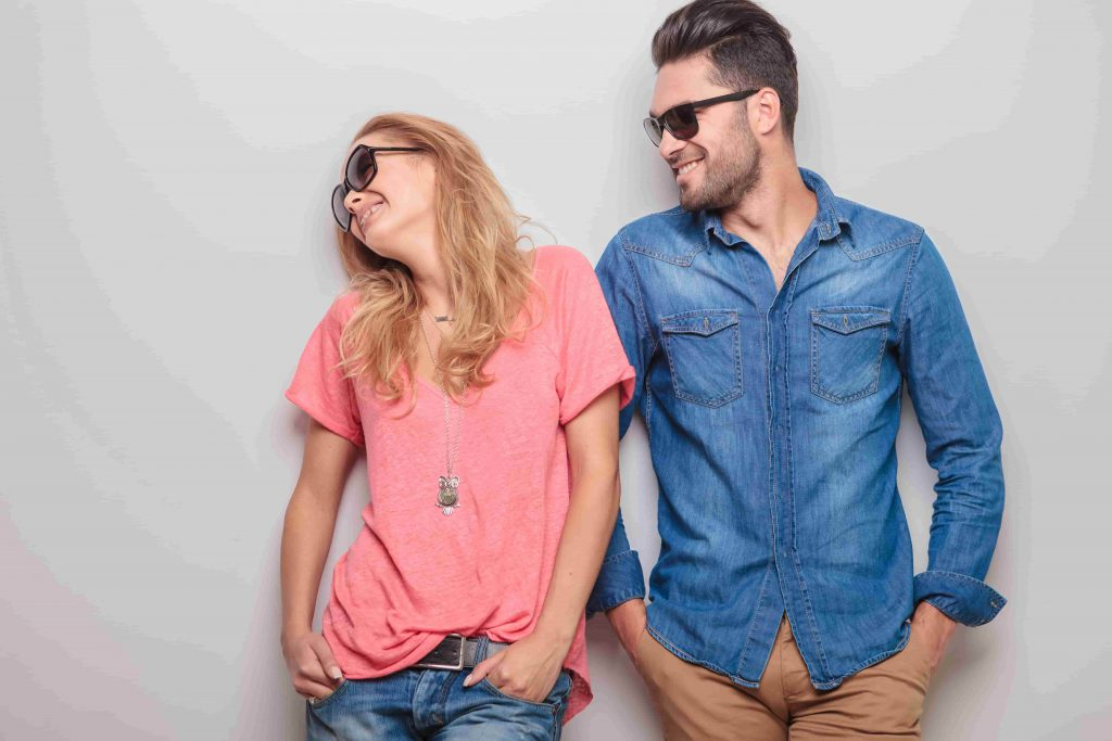 couple leaning against a wall with sunglasses on